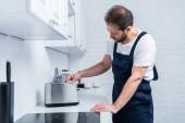 Fotografia artigiano nella lavorazione complessiva fissaggio tostapane nella cucina