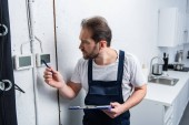 Koncentrovaná dospělých elektrikář s schránky kontrola elektrický panel