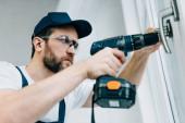 pro dospělé opravář v brýle stanovení popisovač okna elektrickou vrtačkou