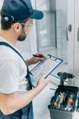 Fotografie Heckansicht des Erwachsenen Mechaniker in Zwischenablage schreiben und überprüfen Fenster
