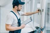 údržbář v brýle drží schránky a kontrola popisovač okna
