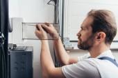 Fotografia concentrati adulto maschio elettricista riparazione scatola elettrica di cacciavite