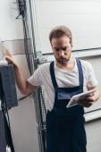 Mann mit Vollbart und digitalem Tablet checkt Stromkasten