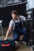 Fotografia adulto maschio artigiano riparazione radiatore acqua e prendendo degli strumenti dalla casella degli strumenti