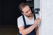 koncentrované vousatý údržbář kontrola elektrický panel
