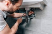 Photo selective focus of male plumber in working overall fixing sink in bathroom