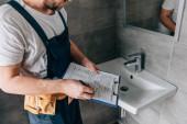 Teilansicht eines männlichen Klempners mit Werkzeuggürtel-Schrift in Klemmbrett nahe kaputtem Waschbecken im Badezimmer
