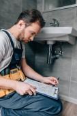Photo bearded male plumber with toolbelt writing in clipboard near broken sink in bathroom