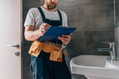 Photo partial view of male plumber with toolbelt writing in clipboard near broken sink in bathroom