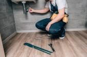 Fotografie Oříznout záběr mužské instalatér s toolbelt opravovat umyvadlo v koupelně