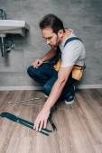 Dospělý samec instalatér brát plyn klíč pro opravu rozbité umyvadlo v koupelně