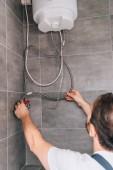 Fotografie zadní pohled na mužské instalatér opravit elektrický bojler v koupelně