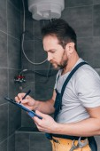 Dospělý samec instalatér psaní do schránky a kontrola elektrický bojler v koupelně