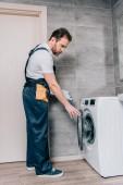 férfi felnőtt szerelőt toolbelt és vágólap ellenőrzése a fürdőszobában mosógép