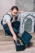 Handwerker holt Werkzeug aus Werkzeugkiste, während er Waschmaschine im Bad repariert