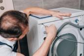 szelektív összpontosít a férfi ezermester fürdőszobában mosógép javítása
