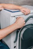 levágott kép a férfi ezermester fürdőszobában mosógép javítása
