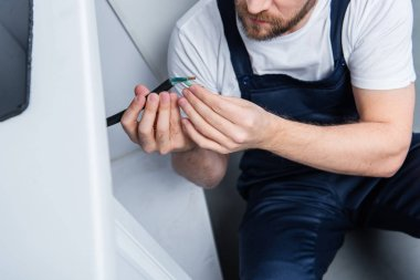 cropped shot of handyman in working overall fixing wires from oven in kitchen