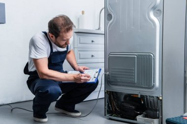 adult craftsman in working overall writing in clipboard near broken refrigerator in kitchen