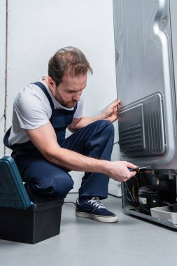 repairman in working overall fixing refrigerator by screwdriver in kitchen