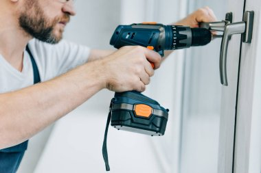 partial view of handyman fixing window handle by electric drill