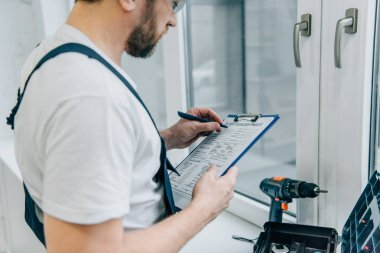 Cropped shot of male handyman writing in clipboard and checking window stock vector