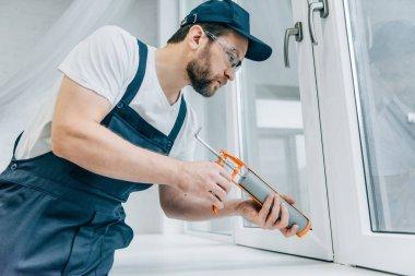 bearded adult repairman fixing window with sealant gun