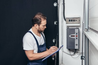 male electrician writing in clipboard and checking electrical box