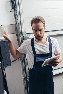 focused male bearded repairman with digital tablet checking electric box