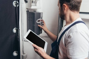 male bearded repairman with digital tablet checking electric box