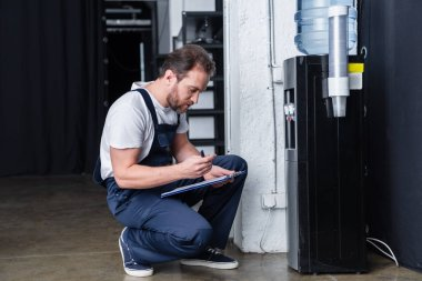 side view of male repairman writing in clipboard during checking of broken water cooler