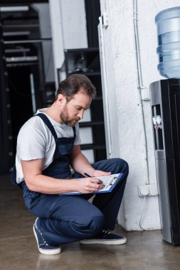male repairman writing in clipboard during checking of broken water cooler
