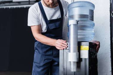 partial view of handyman checking broken water cooler