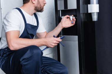 cropped shot of male repairman with clipboard checking broken water cooler