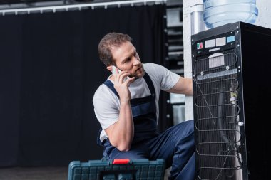 serious male craftsman talking on smartphone during repairing water cooler