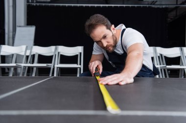 concentrated male craftsman in working overall making measurements of floor by measuring tape