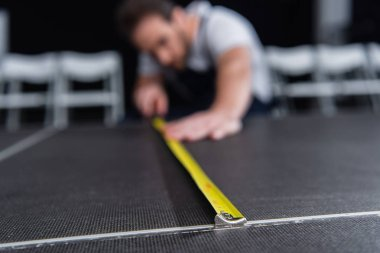 selective focus of male craftsman making measurements of floor by measuring tape