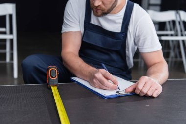 cropped image of male handyman making measurements and writing in clipboard