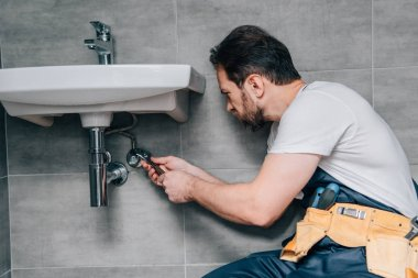 side view of male plumber in working overall fixing sink by spanner in bathroom