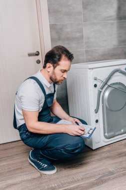 adult handyman writing in clipboard and checking washing machine in bathroom