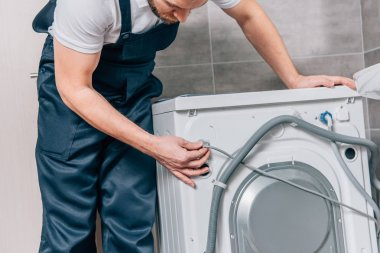 partial view of male handyman repairing washing machine in bathroom