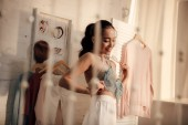 Fotografie selective focus of happy young woman choosing clothes in wardrobe