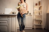 Fotografie cropped shot of happy young woman holding bouquet of beautiful white roses at home