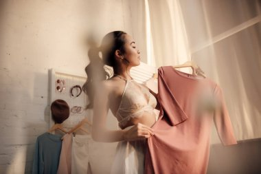 selective focus of beautiful asian woman in underwear holding hanger with stylish dress in wardrobe