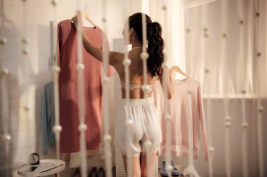 back view of young woman in underwear holding hangers with fashionable clothes in wardrobe