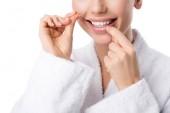 Fotografia vista potata della donna in accappatoio bianco filo interdentale denti isolati su bianco