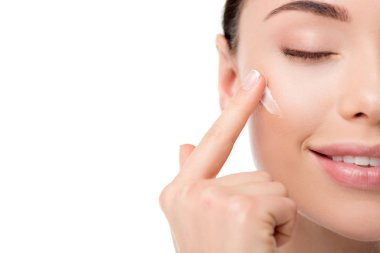 cropped view of woman applying moisturizing face cream isolated on white