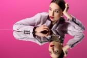 gyönyörű elbűvölő nő a hivatalos viselet tükröző tükrök elszigetelt rózsaszín