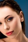 Fotografia Ritratto della donna attraente con trucco affascinante che guarda lobbiettivo isolato sullazzurro