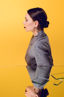 beautiful glamorous woman in formal wear with mirror reflection isolated on yellow